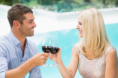 Smiling couple toasting red wine while sitting by swimming pool Royalty Free Stock Images