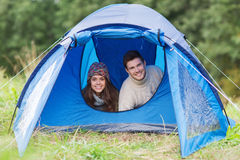 Smiling couple of tourists looking out from tent Royalty Free Stock Image
