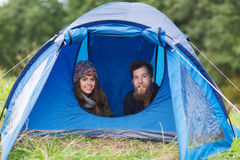Smiling couple of tourists looking out from tent Stock Images