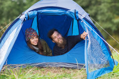 Smiling couple of tourists looking out from tent Stock Photos