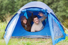 Smiling couple of tourists looking out from tent Royalty Free Stock Photos