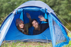 Smiling couple of tourists looking out from tent Stock Photography