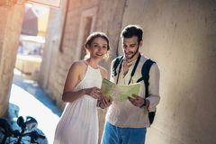 Smiling couple of tourists in sunglasses with map in the city royalty free stock images
