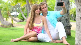 Smiling couple tourists taking self portrait with camera phone under palm tree. Selfie Portrait of Young Attractive Tourist Couple with Phone under Palm tree stock video