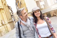 Smiling couple of tourists walking in town Royalty Free Stock Photos