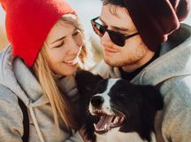 Smiling couple of travelers in cool sunglasses whit cool dog of setting sun. Happy people relax in nature. Back light. royalty free stock images