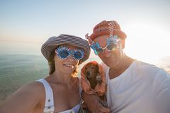 Smiling couple of travelers with small dog. Smiling couple of travelers in funny sunglasses with small dog taking selfie on the beach in rays of setting sun Stock Photography