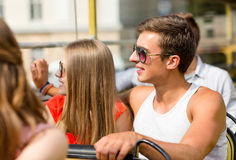 Smiling couple traveling by tour bus. Friendship, travel, vacation, summer and people concept - smiling couple traveling by tour bus Stock Images