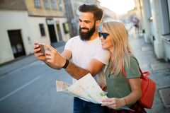 Smiling couple travelling and having fun in the city. Summer holidays, dating and tourism concept. Smiling couple traveling and having fun in the city. Summer stock images