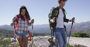 Smiling couple trekking. Two young smiling people walking down from mountain plat with trekking poles on background of mountains stock video