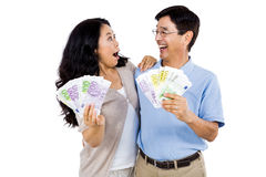 Smiling couple with two fans of cash Royalty Free Stock Photography