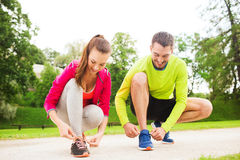Smiling couple tying shoelaces outdoors. Fitness, sport, friendship and lifestyle concept - smiling couple tying shoelaces outdoors royalty free stock photo