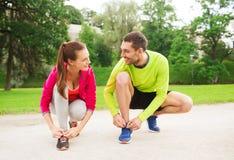 Smiling couple tying shoelaces outdoors Stock Photo