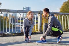 Smiling couple tying shoelaces outdoors Royalty Free Stock Photography