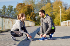 Smiling couple tying shoelaces outdoors. Fitness, sport, people and lifestyle concept - smiling couple tying shoelaces outdoors stock photo