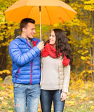 Smiling couple with umbrella in autumn park Stock Photos