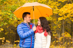 Smiling couple with umbrella in autumn park Stock Photo