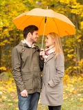 Smiling couple with umbrella in autumn park Royalty Free Stock Images