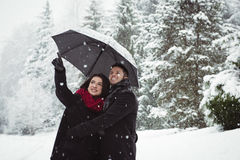 Smiling couple under umbrella pointing at view in forest Stock Photography
