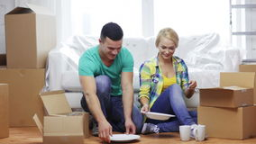 Smiling couple unpacking boxes with kitchenware stock video footage