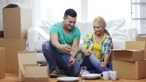 Smiling couple unpacking boxes with kitchenware stock video
