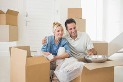 Smiling couple unpacking boxes in a new house Stock Photo