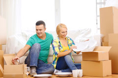 Smiling couple unpaking boxes with kitchenware Stock Images
