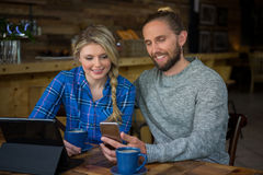 Smiling couple using cellphone at table in cafe Stock Image