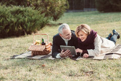 Smiling couple using digital tablet Royalty Free Stock Photography