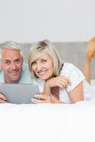 Smiling couple using digital tablet in bed Stock Photo