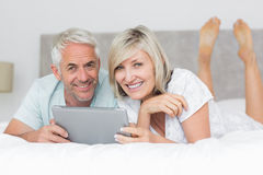 Smiling couple using digital tablet in bed Stock Images