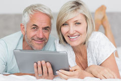 Smiling couple using digital tablet in bed Stock Photos