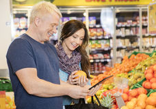 Smiling Couple Using Digital Tablet While Choosing Oranges Royalty Free Stock Photos