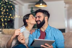 Smiling couple using digital tablet and credit card. At home royalty free stock photos