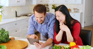 Couple using digital tablet in kitchen at home 4k. Smiling couple using digital tablet in kitchen at home 4k stock video