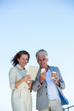 Smiling couple using digital tablet and mobile phon Royalty Free Stock Photography
