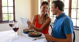Smiling couple using a digital tablet in restaurant. Smiling couple talking to each other and using a digital tablet in restaurant 4K stock video footage