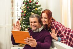 Couple with digital tablet at christmastime. Smiling couple using digital tablet while sitting together on sofa at christmastime stock photos