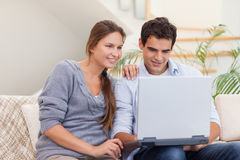 Smiling couple using a laptop Royalty Free Stock Photos