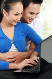 Smiling couple using a laptop Royalty Free Stock Photography