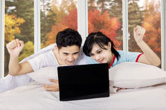 Smiling couple using laptop on bedroom Royalty Free Stock Photos