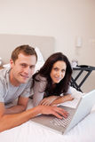 Smiling couple using laptop in the bedroom together Royalty Free Stock Images