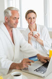 Smiling couple using laptop at breakfast in bathrobes Royalty Free Stock Photo