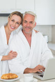 Smiling couple using laptop at breakfast in bathrobes Stock Photos