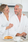 Smiling couple using laptop at breakfast in bathrobes Stock Image