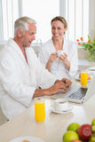 Smiling couple using laptop at breakfast in bathrobes Stock Images
