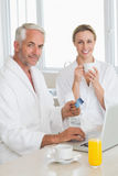 Smiling couple using laptop at breakfast in bathrobes Royalty Free Stock Images