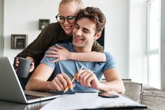 Smiling couple using laptop computer at home. Smiling lady in glasses using laptop computer and hugging her concentrated men at home Stock Image