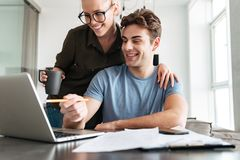 Smiling couple using laptop computer at home. Smiling lady in glasses using laptop computer and hugging her concentrated men at home Stock Photo