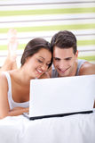 Smiling couple using laptop Royalty Free Stock Images